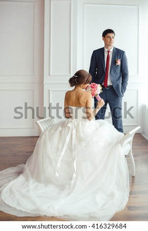 Wedding couple in love. Beautiful bride in white dress with brides bouquet and handsome groom in blue suite posing indoors in decorated studio room, white bright interior with big window.  - stock photo