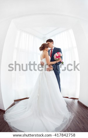Wedding couple in love. Beautiful bride in white dress with brides bouquet and handsome groom in blue suite standing and embracing each other indoors at home, white bright room with big window High - stock photo