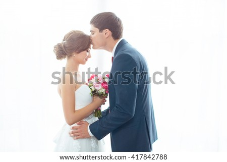 Wedding couple in love. Beautiful bride in white dress with brides bouquet and handsome groom in blue suite standing and embracing each other indoors at home, white bright isolated background. Husband - stock photo