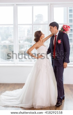 Wedding couple in love. Beautiful bride in white dress with brides bouquet and handsome groom in blue suit standing and embracing each other indoors in decorated studio room, white bright interior - stock photo