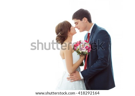 Wedding couple in love. Beautiful bride in white dress with brides bouquet and handsome groom in blue suit standing and embracing each other indoors at home, white bright isolated background - stock photo