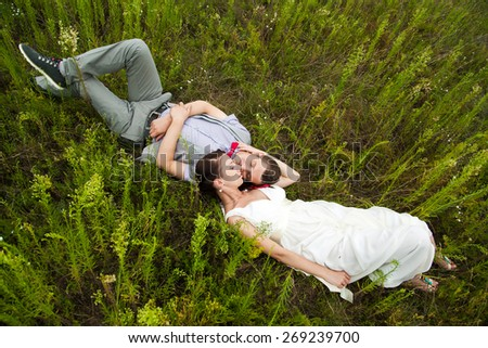 wedding couple in love lying in green grass in summer meadow. happy bride and groom relaxing outside