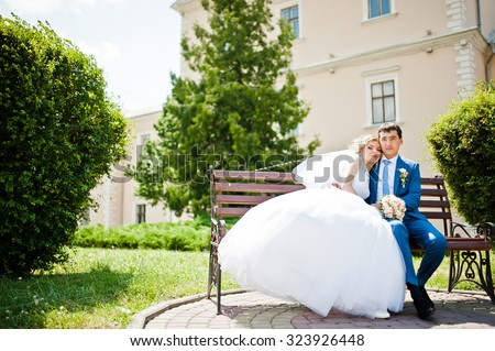 wedding couple in love sitting on bench - stock photo