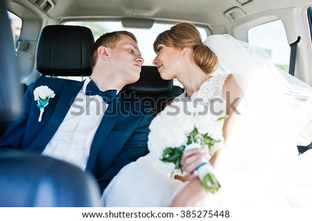 Wedding couple in the back seat of car - stock photo