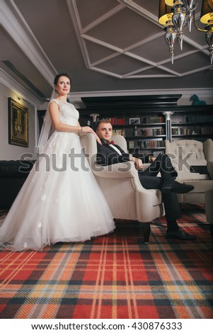 Wedding couple indoors is hugging each other. Beautiful model girl in white dress. Man in suit. Beauty bride with groom. Female and male portrait.