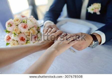 Wedding couple is holding hands. Beauty bride with groom. Beautiful model girl in white dress. Man in suit. Female and male portrait. Woman with lace veil. Cute lady and guy indoors