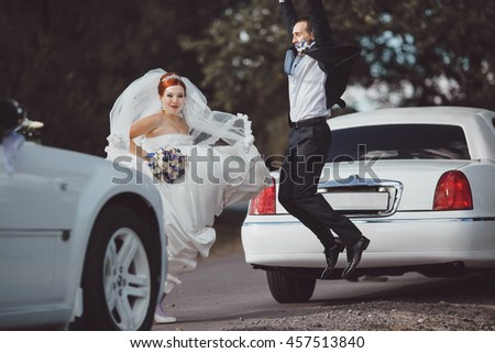wedding couple jumping next to white limo at countryside