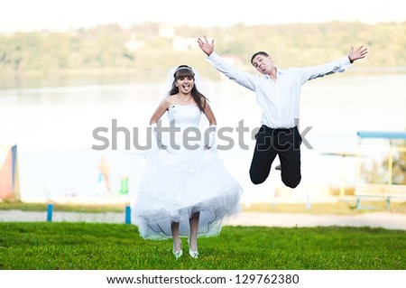 Wedding couple jumping on the green grass - stock photo