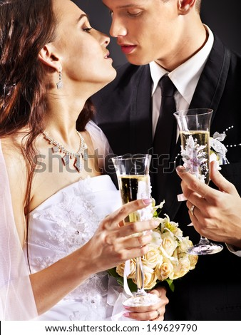 Wedding couple kissing and drinking champagne.