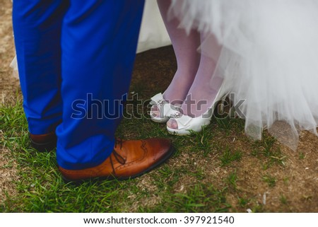 Wedding couple on the country road. Groom shoes, bridesmaid shoes with open nose - stock photo