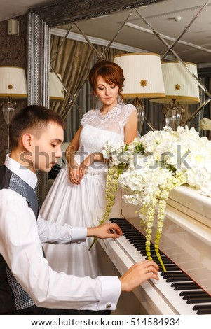 wedding couple playing on a piano in banquet room