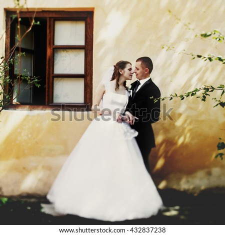 Wedding couple poses in the front of old wooden window