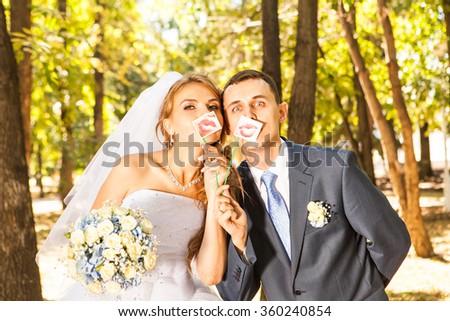 Wedding couple posing with stick lips, mask - stock photo