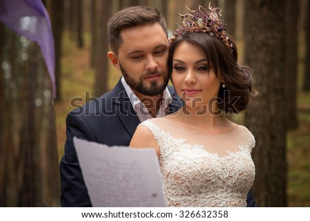 Wedding couple reads the oath on the paper - stock photo