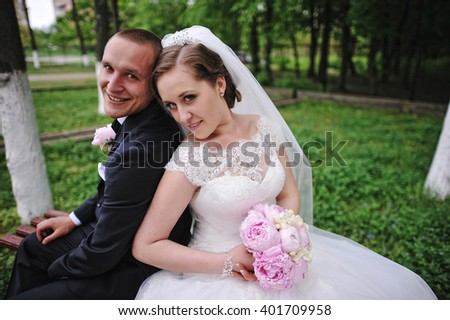 Wedding couple sitting on bench leaning backs to each other - stock photo