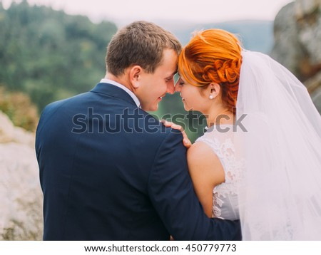 Wedding couple softly embracing at rocky mountains against the sky. Cute romantic moment. Back view