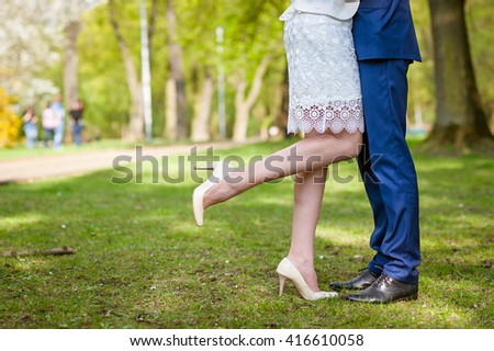 Wedding couple standing in the park on grass. Focus on legs - stock photo