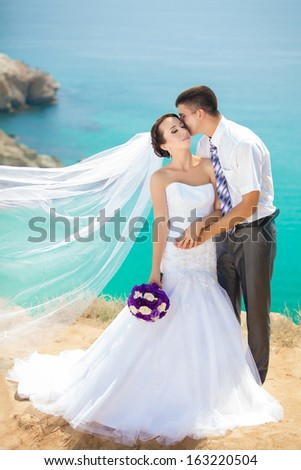 wedding couple stands on a cliff, blue sea on background