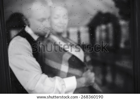 Wedding couple together close to each other at the window - stock photo