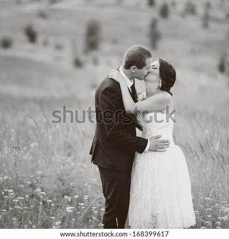 Wedding couple together in field. Black and white.
