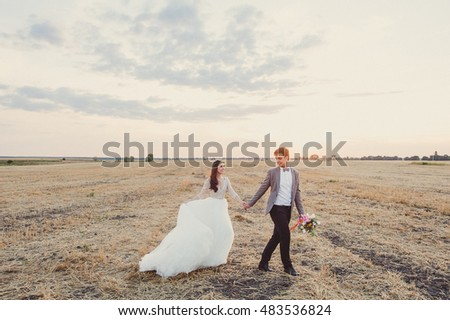 Wedding couple walking in a field. Walk at sunset