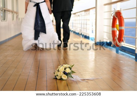 Wedding couple walking in the distance with bouquet in front on a deck of a cruise ship - stock photo