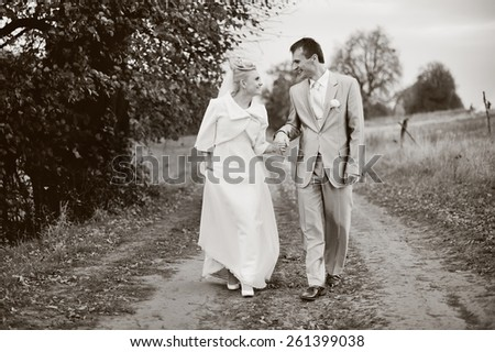 Wedding couple walking together at countryside.