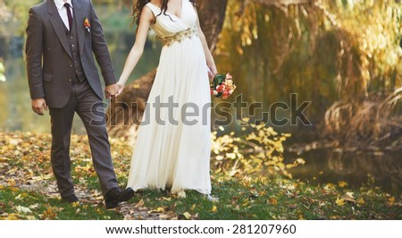 Wedding couple walking together in autumn forest. Fim effect color type.