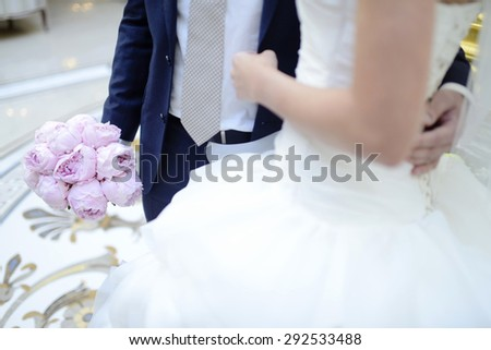 Wedding couple with bouquet. Female and male portrait. Beautiful model girl in white dress. Man in suit. Beauty bride wi¬th groom. Woman in bridal gown. Cute lady and guy indoors - stock photo
