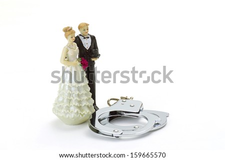 Wedding Couple with handcuffs on bright background - stock photo