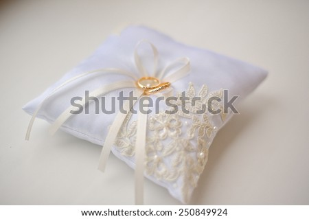 Wedding cushion with gold rings. - stock photo