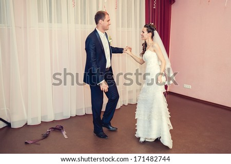 wedding dance of bride and groom. Kiss and dance young bride and groom in banqueting hall - stock photo