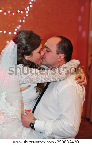 wedding dance of bride and groom. Kiss and dance young bride and groom in dark banqueting hall - stock photo