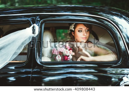 Wedding day. Bride sitting in wedding car, looking at window and holding bouquet. Decorations. Waist up