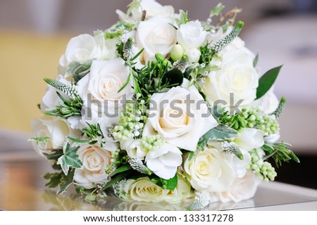 Wedding day closeup of brides bunch of white roses