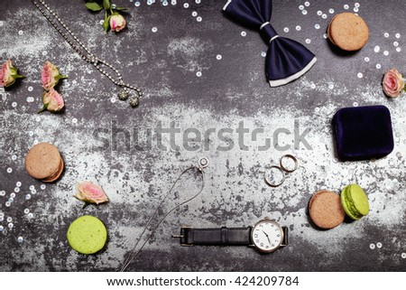 Wedding day concept. White gold luxury necklace, macaroones, two wedding rings on the velvet box, deep blue bowtie, roses, lipstick and men's watch on the table. Place for text. - stock photo