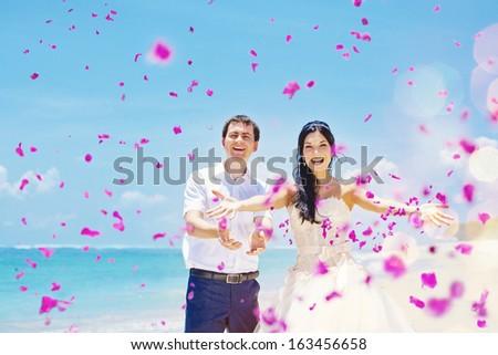 wedding day - couple with plenty of petals - stock photo
