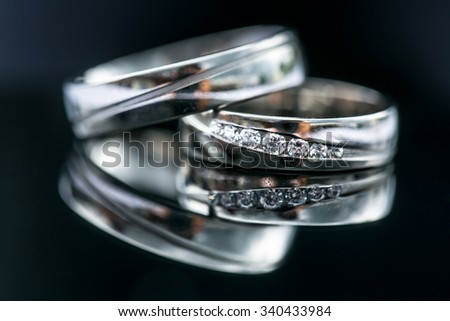 Wedding day details - two lovely golden wedding rings awaiting their moment, with some nice reflections - stock photo