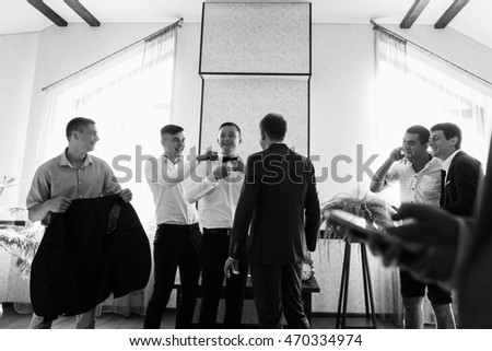 Wedding day. Groom and groomsmen at luxury apartment. Groomsmen to help prepare the groom for the wedding ceremony. Wedding concept