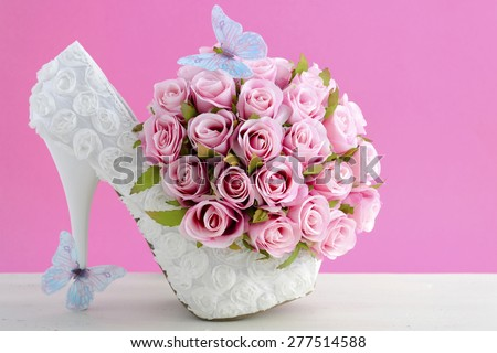 Wedding day pink and white bouquet of silk roses with blue butterflies and white high heel shoe.  - stock photo