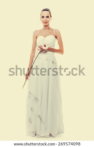 Wedding day. Portrait of happy blonde woman young attractive bride in formal white gown with pink flower gerbera daisy  instagram filter. Studio shot