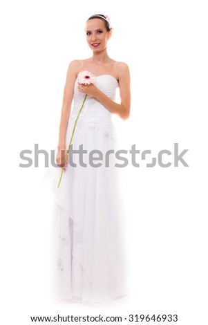 Wedding day. Portrait of happy blonde woman young attractive bride in formal white gown with pink flower gerbera daisy isolated. Studio shot