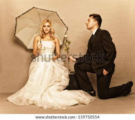 Wedding day. Portrait of romantic married couple blonde bride with umbrella and enamored groom giving a rose to girl. Full length studio shot sepia color, vintage photo - stock photo