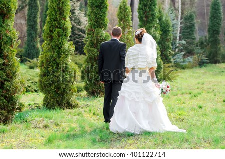 Wedding day. The groom and the bride walk on park.  - stock photo