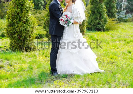 Wedding day. The groom and the bride walk on park. The groom embraces the bride. - stock photo