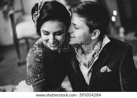 Wedding. Decor. Bride. The bride's bouquet. Artwork. Bride in blue-white dress and the groom in a suit sitting on a gray cloth on a background of textured gray wall, vintage chairs and an easel