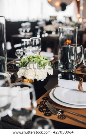 Wedding decor. Green and white hydrangea flowers in vase with cutlery and tableware on foreground. Reception.  - stock photo