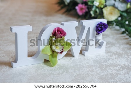 Wedding decor, LOVE letters and flowers on table. Fresh flowers and LOVE decoration on festive table. Luxurious wedding decoration on restaurant table. Elegant event - stock photo