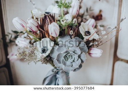 Wedding. Decor. The bride's bouquet. Artwork. Wedding bouquet of white, pink, and green is in the vintage white chair against a background of a gray textured wall - stock photo