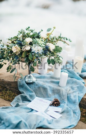 wedding decor with a bouquet and candles on the stones of the Carpathian waterfall